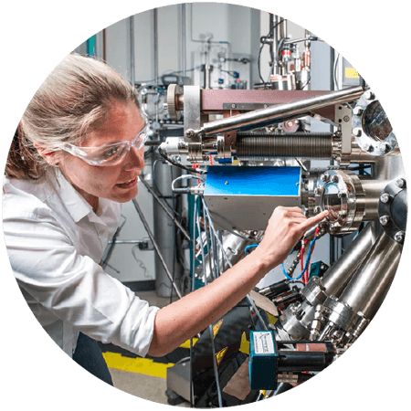 Woman wearing safety goggles pointing at machine