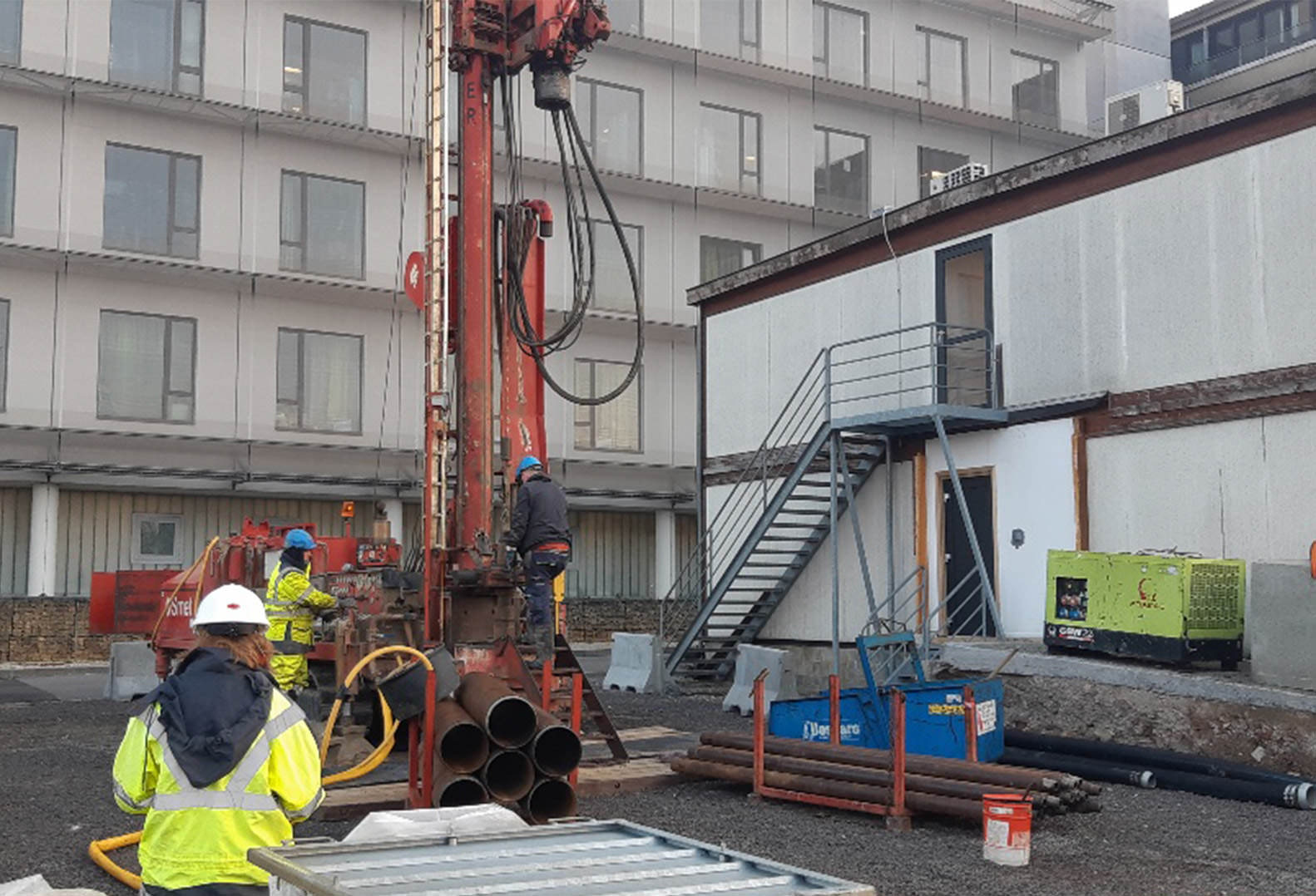 Three people work on the drilling phase of a geothermal well