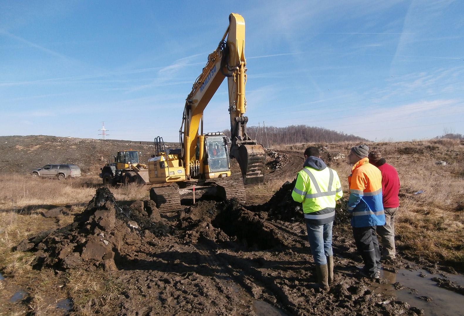 Three men with heavy machinery standing on Belgium landfill site