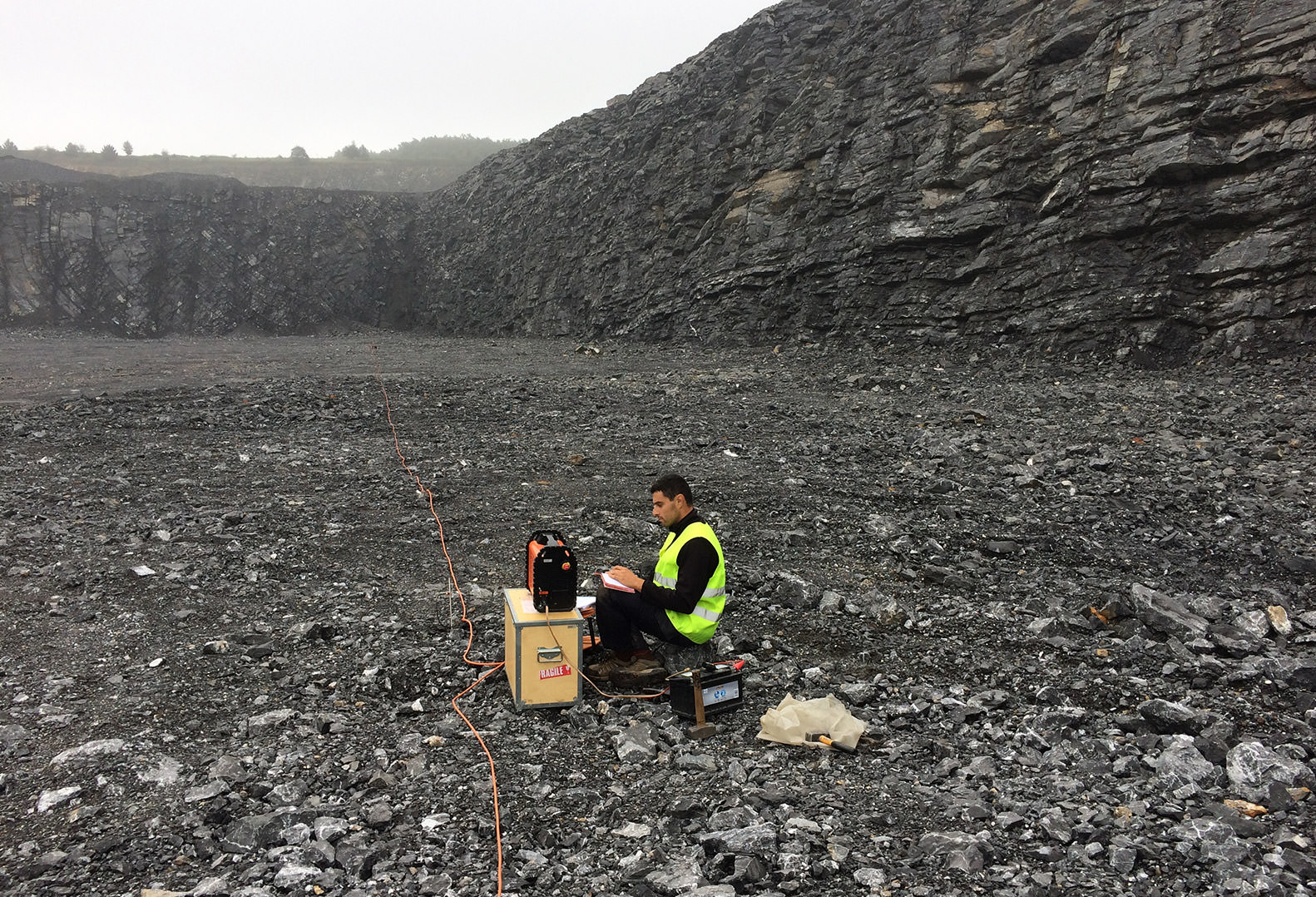 Man wears Hi-Vis vest whilst performing geophysical data acquisition in quarry
