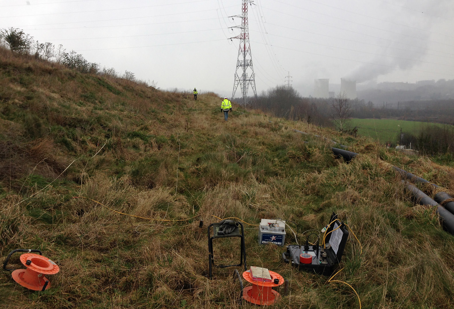 Two men in Hi-Vis perform Geophysical Data Acquisition on Belgium property